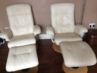 Two cream leather swivel/ recliner chairs with foot stools.