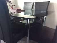 Brand new Harveys Glass Boat Table & 6 black faux leather chairs