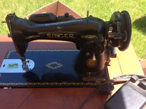 Antique Singer sewing machine in cabinet with bench