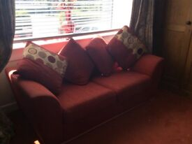 Rust sofa bed with four cushions