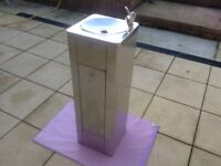 A PEDESTAL FLOOR STANDING DRINKING FOUNTAIN WITH LOCKABLE CABINET.