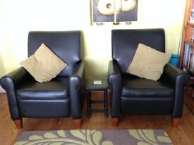 Two black faux leather reclining chairs