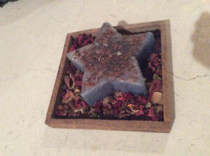 Antiqued homemade star candle in wooden tray with potpourri