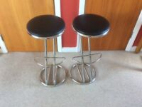 A pair of chrome and black faux leather kitchen bar stools.