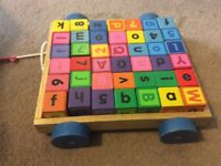 Wooden alphabet and number blocks on a pull along trolley