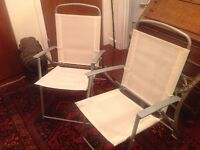 A pair of cream folding chairs