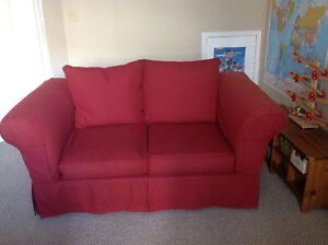Really well made love seat with red slipcover