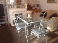 Glass topped table & four chairs