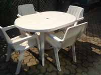 White plastic garden table and chairs and umbrella with stand