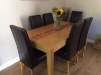 Oak veneer dining table with six brown leather chairs