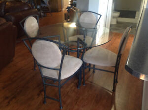Glass top wrought iron table and 4 taupe microfibre chairs.