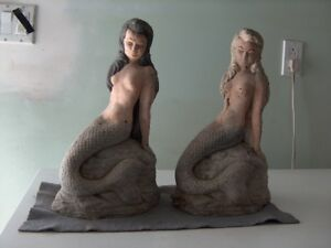 Two small cement mermaids