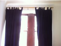 Long blue curtains with curtain pole