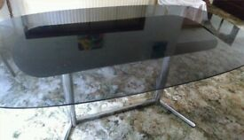 Glass-topped dining table with stainless steel base.