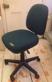 Comfortable moveable dark green office chair on wheels with adjustable seating