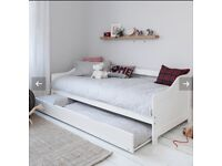 White wooden bed with pullout trundle