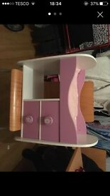 Pink wooden dolls bed.