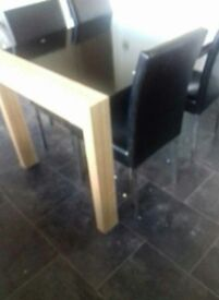 black glass and wood dining table with four chairs