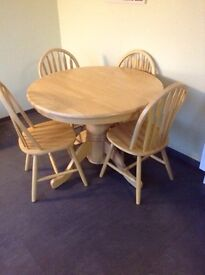 Round extending table with four wheel back chairs