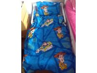 Toddler bed with mattress, duvet, pillow and toy story bedding. Like new