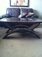 2 solid wood tables with glass tops.