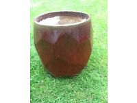 large unusual glazed terracotta plant pot in burgundy