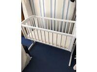 White swinging crib with mattress