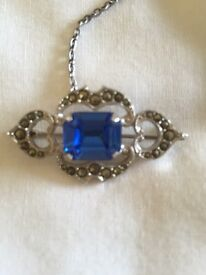 Antique brooch with blue sapphire colour stone safety chain & pin .