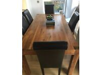 Elegant medium wood long dining table and 6 black leather high back chairs.