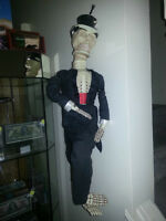 freaky skeleton guy in tux plays a funky beat and eyes light up.