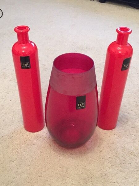 Set of three red vases, one large opening and the two vases with smaller openings