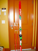 Two pairs downhill skis and poles, one pair heated boots