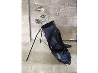 Navy Ping golf bag with assorted golf clubs