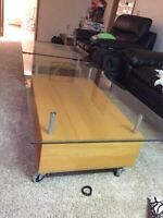 2 glass and wood Coffee tables on wheels $250 firm.  Airdrie