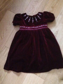 Maroon velvet party dress with buttons on the back .