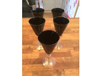 9 black wine glasses and 2 tall glasses