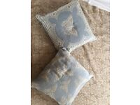 Two blue and cream butterfly cushions