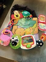 Assorted baby rattles , toys , book and head rest for car seat