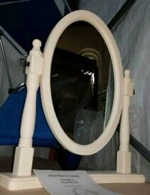 A brand new cream wooden dressing table mirror.