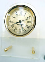 Alarm clock made clear plastic, leans on 2 gold posts