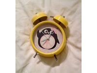 YELLOW TWO BELL RETRO ALARM CLOCK WITH PENGUIN DESIGN. VERY GOOD CONDITION