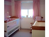 Cot bed with mattress and fully lined baby pink curtains.