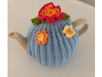Pale blue knitted tea cosy with summer flowers