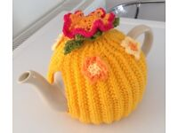 Yellow knitted tea cosy with summer flowers.