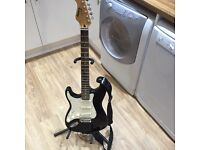 Electric guitar with amp, stand, case, automatic tuner and spare strings