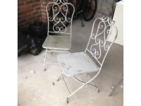 Pair of ornate metal garden chairs
