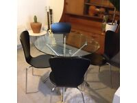 Glass dining table circular with black chairs modern