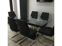 Designer glass table and leather and satin chrome chairs