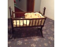 Dark wood cradle comes with three different quilts and curtains also bumpers
