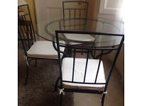 Wrought iron glass top table & 4 chairs with cream cushions